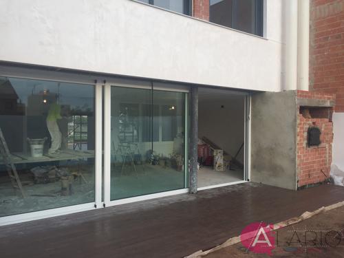 Ventanal de fachada trasera con pavimento de terraza colocado en construcción de vivienda unifamiliar